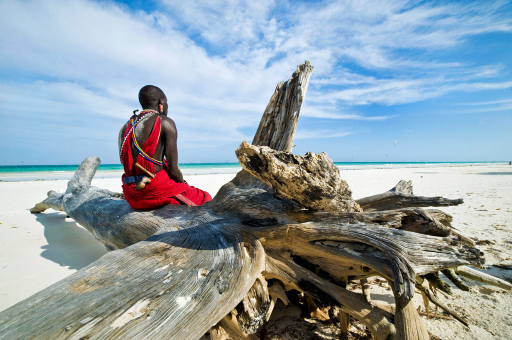 Maasai sitting by the ocean on the beach